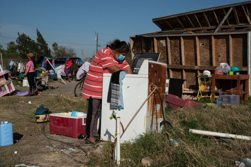 Erika Aguilar, 40, a mother of three, takes out clothes from the washer at her home in Edinburg, Texas. Her kitchen, as seen behind her, rolled over during hurricane Hanna last summer. Credit... Verónica G. Cárdenas