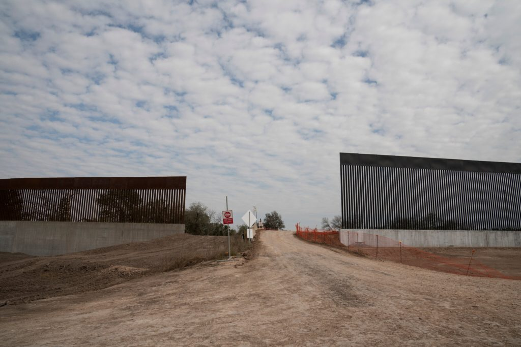 A gap where a gate will typically go is seen near Alamo, Texas. The taller wall on the right is part of the newer wall where former former President Donald Trump visited in early January. Credit... Verónica G. Cárdenas
